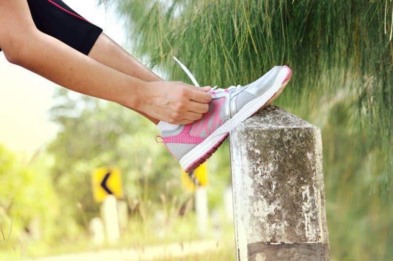 Крупный план женщины связывая шнурки ботинка стоковое фото