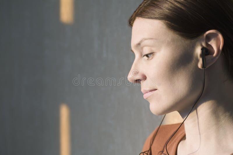Крупный план женщины слушая к музыке стоковые изображения rf