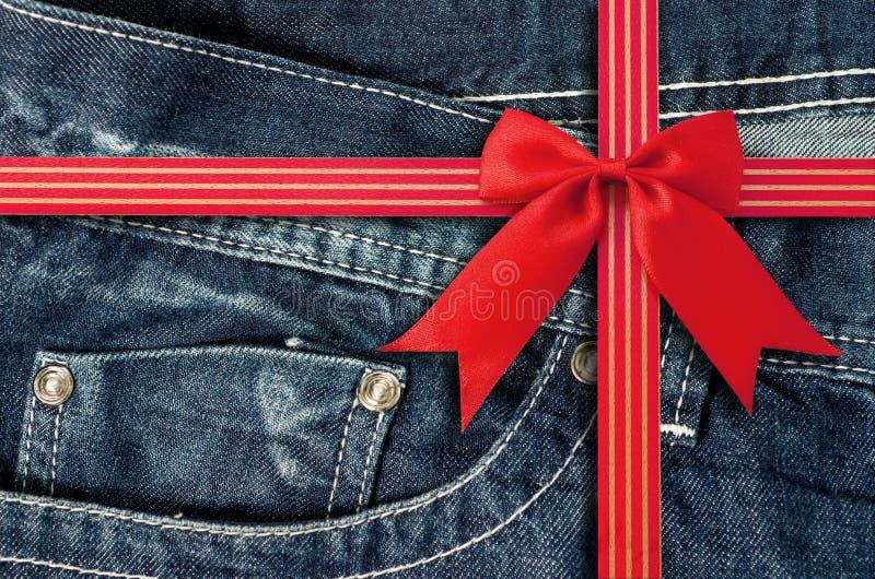 Крупный план джинсовой ткани карманный с красным смычком стоковая фотография rf
