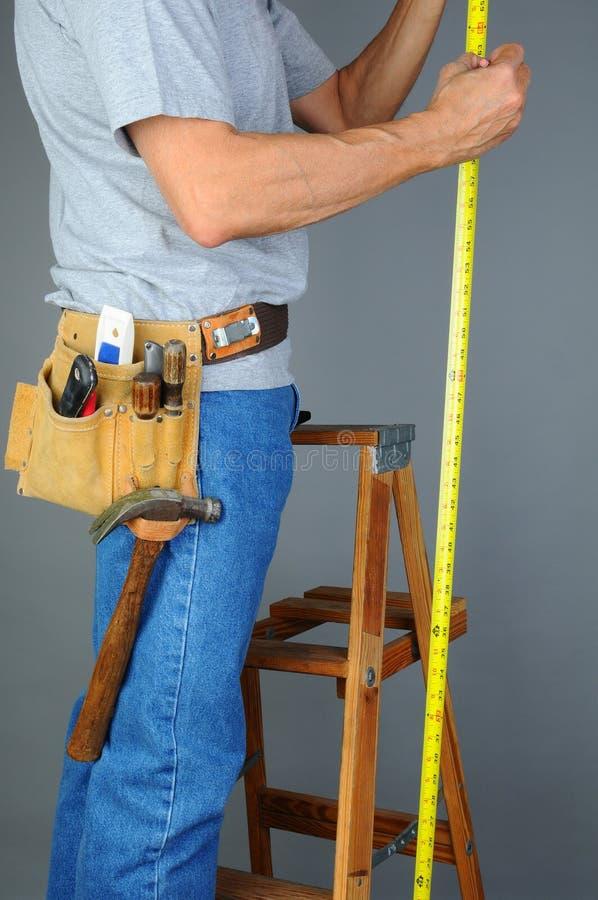 Контрактор стоя на измерять трапа стоковая фотография