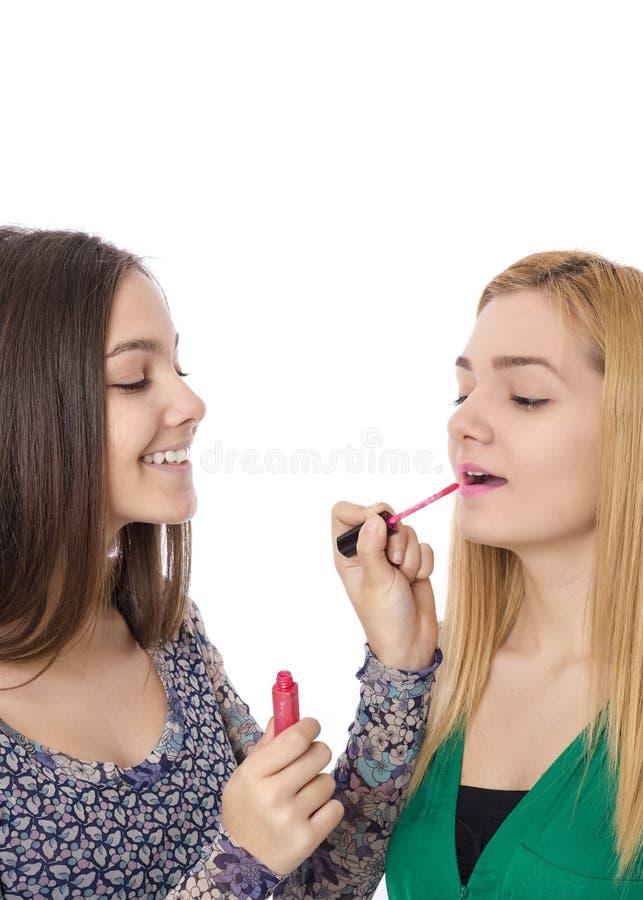 Крупный план красивого подростка брюнет прикладывая губную помаду к нему стоковые изображения