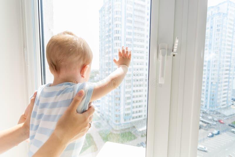 Крупный план матери держа ребёнок пока он смотрит внешний t стоковое изображение