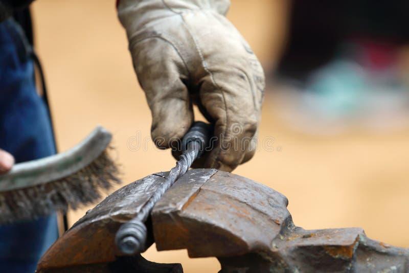 Крупный план металла кузнеца почищенного щеткой рукой выковал продукты стоковое изображение