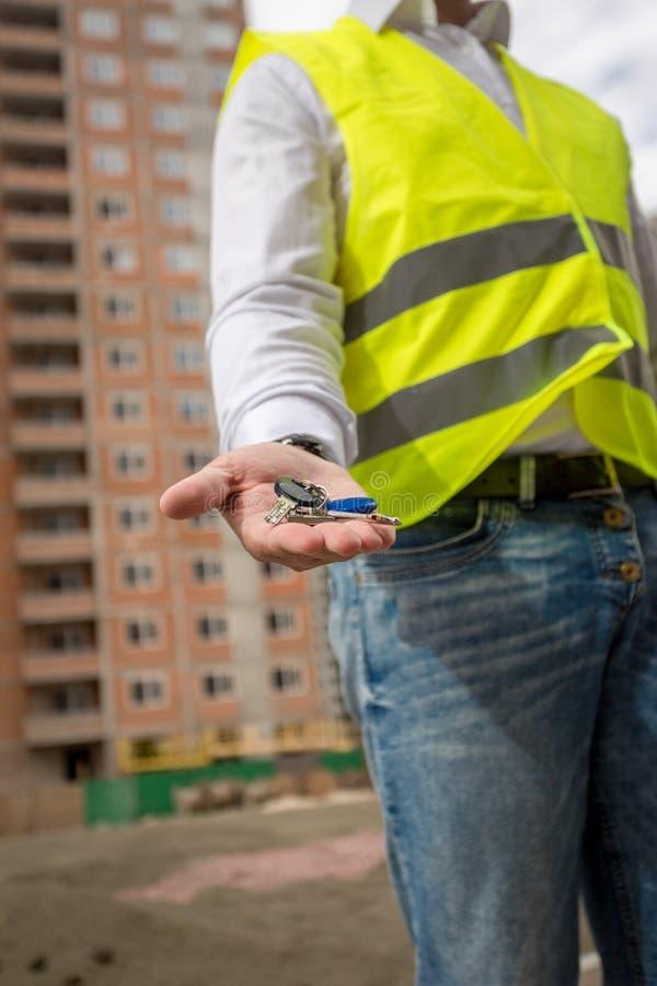Крупный план молодого инженера по строительству и монтажу держа ключи от нового hom стоковое фото