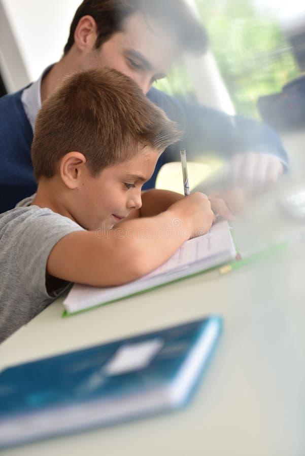 Крупный план молодого мальчика с его домашней работой сочинительства отца стоковая фотография