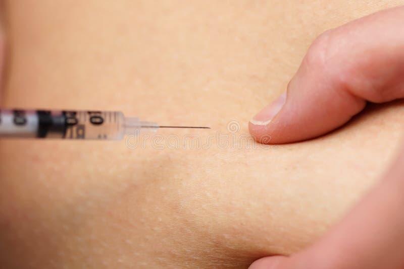 Крупный план молодой женщины давая съемку инсулина стоковая фотография