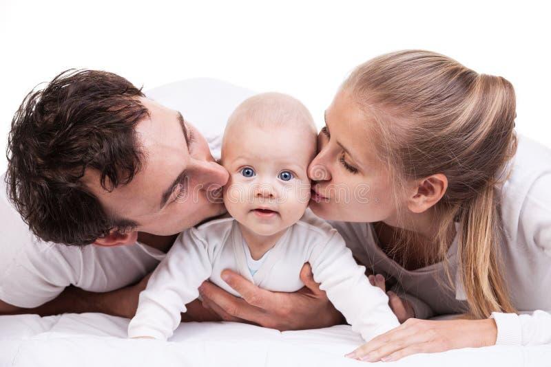 Крупный план молодой семьи с ребёнком над белизной стоковое изображение rf