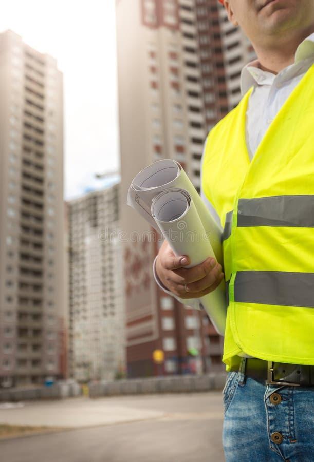 Крупный план мужского инженера по строительству и монтажу представляя на высоком здании на стоковая фотография