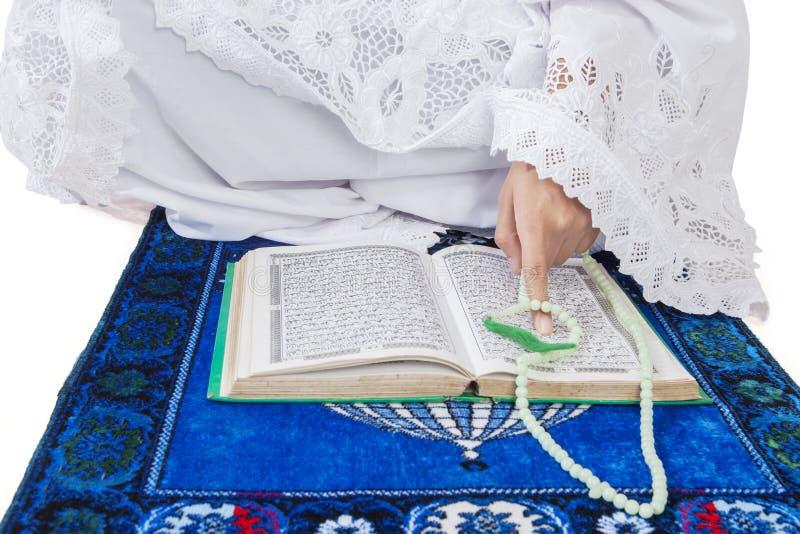 Крупный план мусульманской женщины читая Koran стоковые изображения