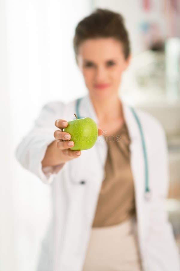 Крупный план на женском doctorдавая зеленое яблоко стоковые фото