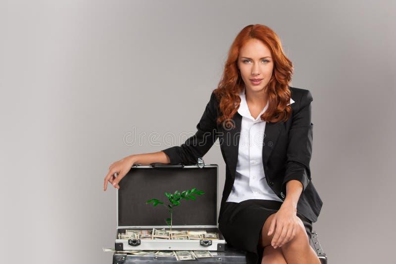 Крупный план на женщине сидя на чемодане вполне денег стоковое фото