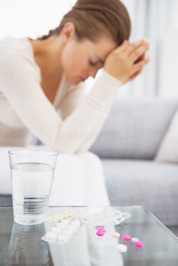 Крупный план на медицине на таблице и чувствуя плохой женщине в предпосылке стоковая фотография rf