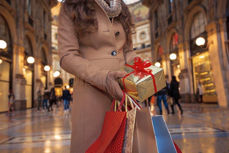 Крупный план на подарке и хозяйственных сумках рождества в руках женщины стоковые изображения