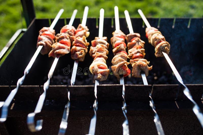 Крупный план некоторых протыкальников мяса будучи жаренным в барбекю outdoors стоковые фото