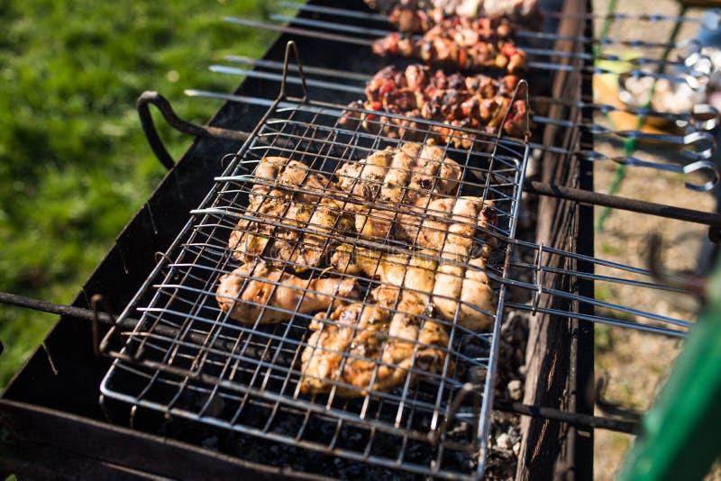 Крупный план некоторых протыкальников мяса будучи жаренным в барбекю Жарить marinated shashlik на гриле стоковое изображение rf
