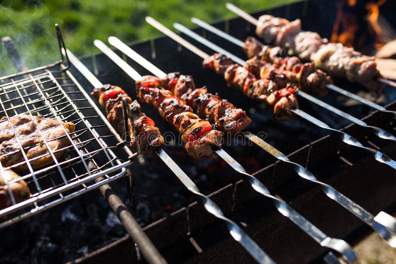 Крупный план некоторых протыкальников мяса будучи жаренным в барбекю outdoors стоковые фотографии rf
