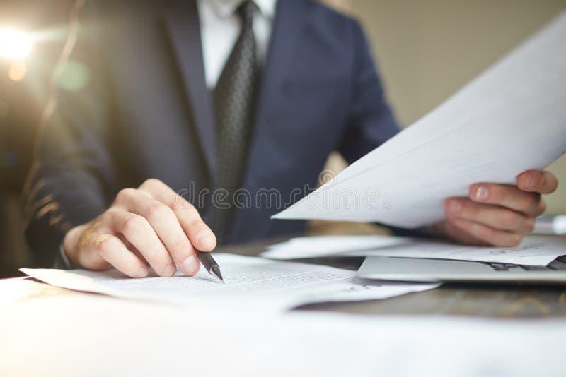 Крупный план обработки документов бизнесмена рассматривая стоковое фото