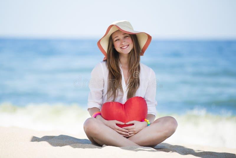Крупный план довольно молодой усмехаясь женщины с сердцем игрушки стоковое изображение rf