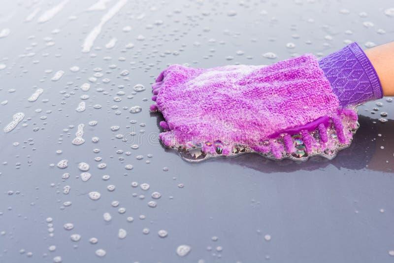 Крупный план очищая его автомобиль используя мойку перчаток стоковые фотографии rf