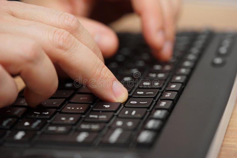 Крупный план пальцев печатая на клавиатуре компьютера стоковые фото