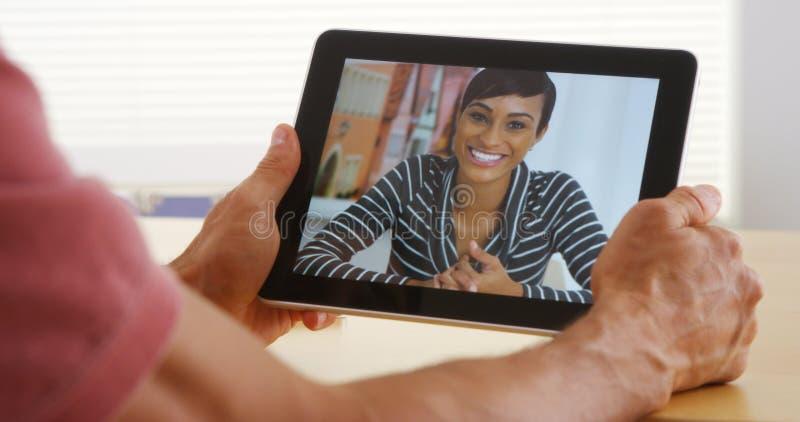 Крупный план привлекательной африканской женщины говоря на таблетке стоковая фотография rf
