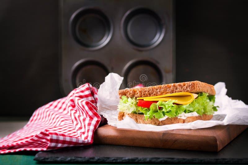 Крупный план провозглашанного тост сандвича с листьями, томатами и сыром салата с вилкой на разделочной доске на темной предпосыл стоковые фото