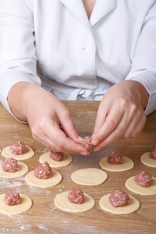 Крупный план рук кашевара на круглом тесте кладет завалку мяса стоковое изображение