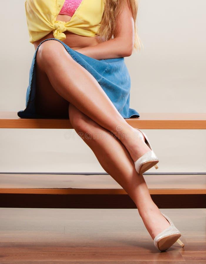 Крупный план сексуальных ног женщины в высоких пятках и юбке стоковая фотография rf