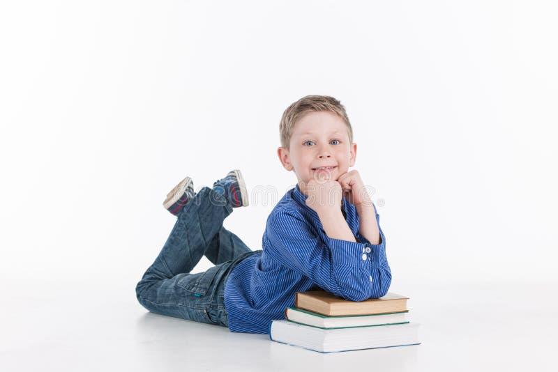 Крупный план склонности мальчика на книгах стоковое фото rf