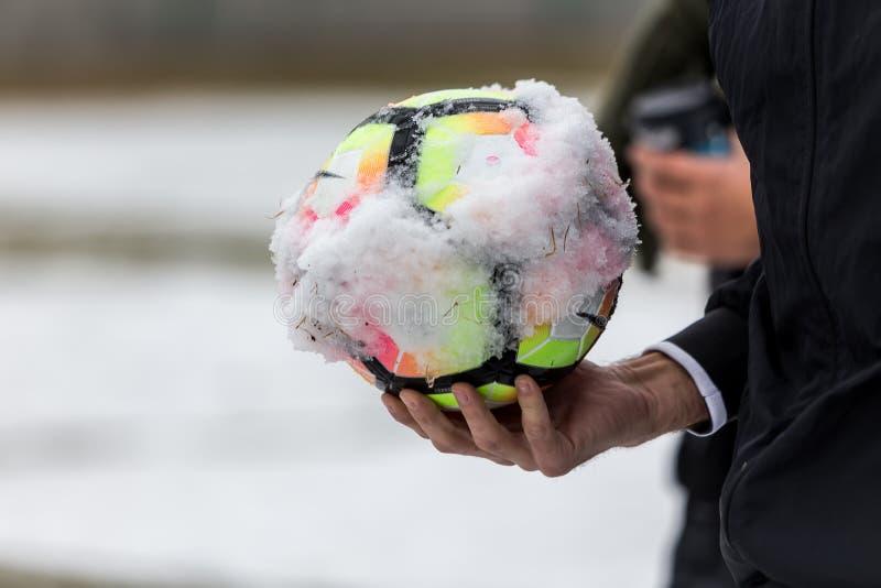Крупный план снежного футбольного мяча и руки ` s рефери стоковое фото rf