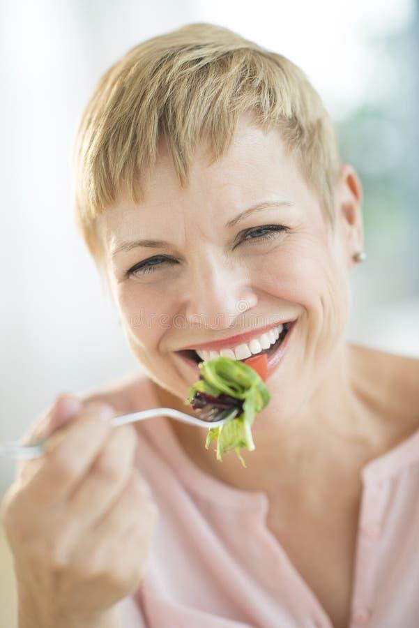 Крупный план счастливой женщины есть Vegetable салат стоковые изображения rf