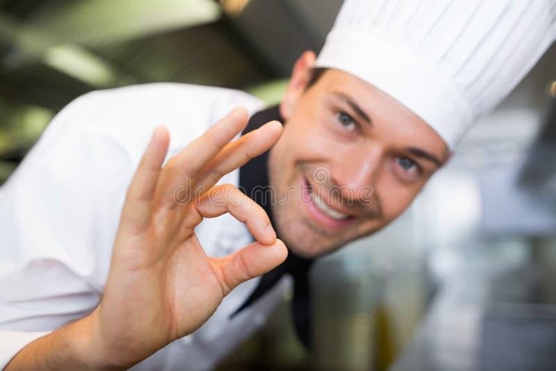 Крупный план усмехаясь мужского кашевара показывать одобренный знак стоковое фото