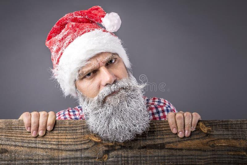 Крупный план хмурясь человека при замороженная борода нося santa красный ca стоковое изображение rf