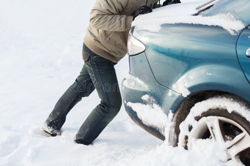 Крупный план человека нажимая автомобиль вставил в снеге стоковое изображение rf