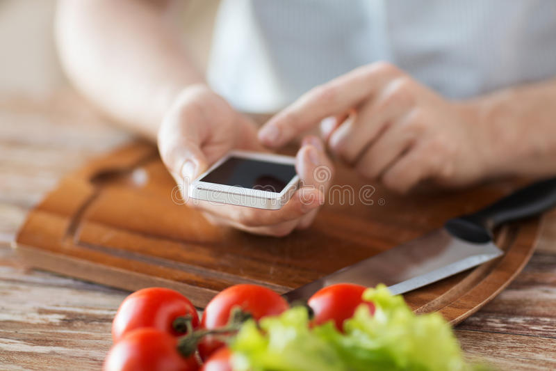 Крупный план человека указывая палец к smartphone стоковая фотография