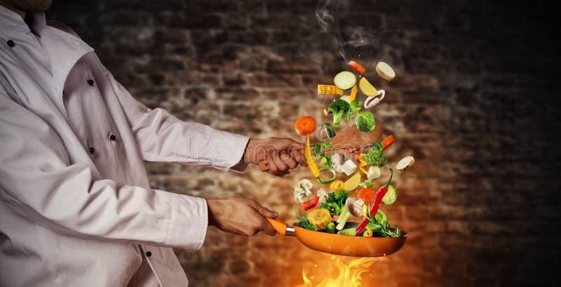 Крупный план шеф-повара подготавливая овощ на лотке стоковое изображение