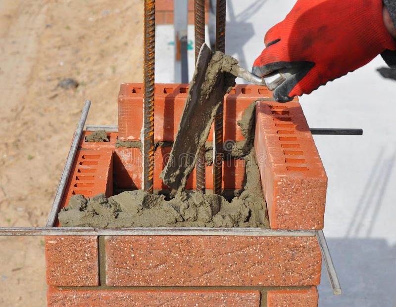 Крупный план Bricklaying Рука каменщика держа нож замазки стоковое фото