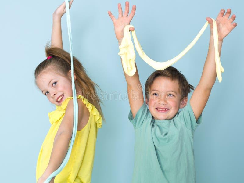Крутой, милый мальчик и его старшая сестра играют с домодельным шламом перед голубой предпосылкой и имеют много потеху стоковые фотографии rf
