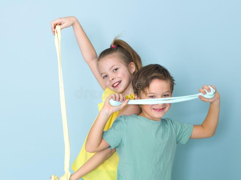 Крутой, милый мальчик и его старшая сестра играют с домодельным шламом перед голубой предпосылкой и имеют много потеху стоковые изображения rf