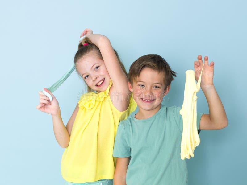 Крутой, милый мальчик и его старшая сестра играют с домодельным шламом перед голубой предпосылкой и имеют много потеху стоковое изображение rf