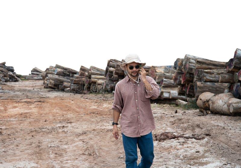 крутой человек 30s-40s с солнечными очками и связь портрета шляпы с мобильным телефоном на предпосылке места природы полесья стоковые фото