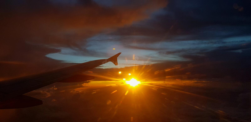 Крыло воздушных судн или самолета на темном небе с предпосылкой пирофакела света захода солнца стоковые фото