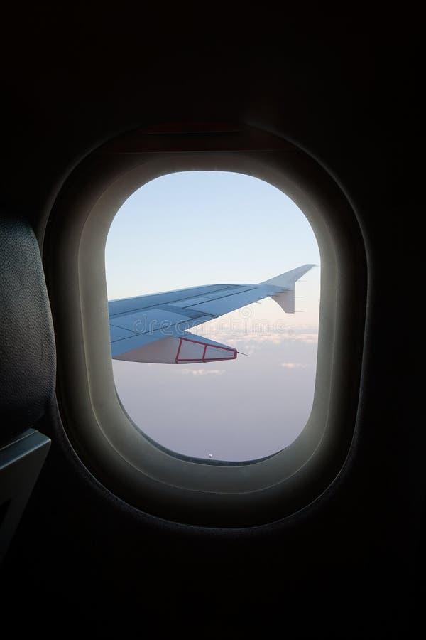 Крыло и облака в иллюминаторе ` s воздушных судн стоковая фотография