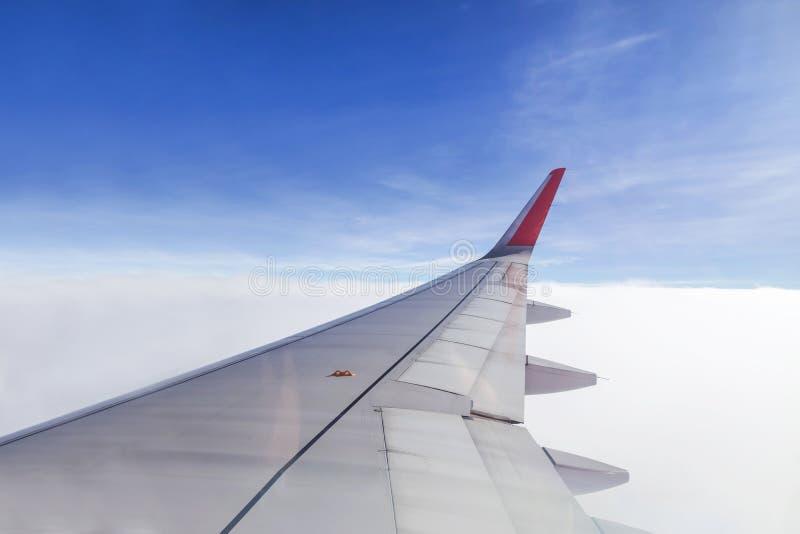 Крыло коммерчески взгляда самолета от права окно плоского летания над облаками на голубом небе стоковые изображения