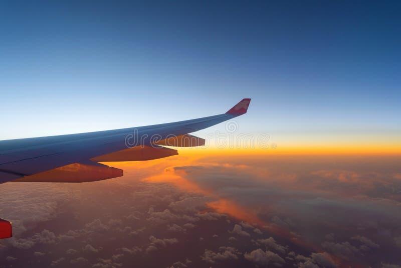 Крыло летания самолета над облаками утра с небом на стоковая фотография
