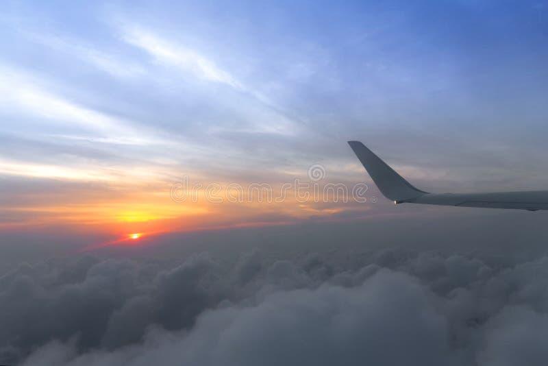 Крыло самолета воздуха на море предпосылки неба захода солнца облака от самолета окна стоковые фотографии rf