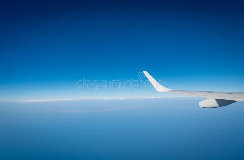 Крыло самолета над белыми облаками Летание самолета на голубом небе Сценарный взгляд из окна самолета Полет коммерческой авиакомп стоковая фотография