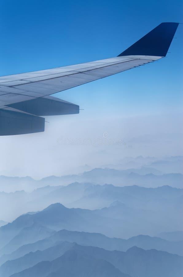 Крыло самолета над горами в тумане стоковая фотография