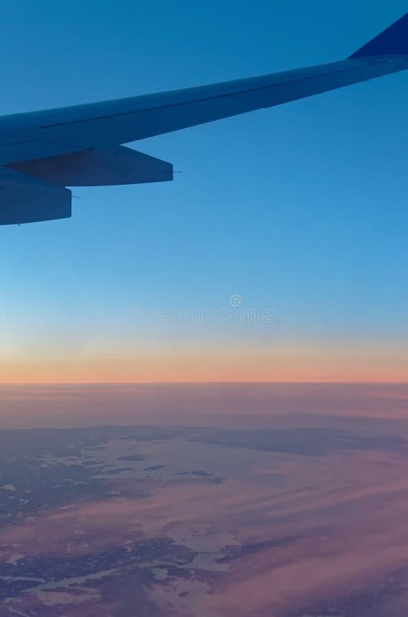 Крыло самолета над ландшафтом и облачным небом на заходе солнца стоковые фото