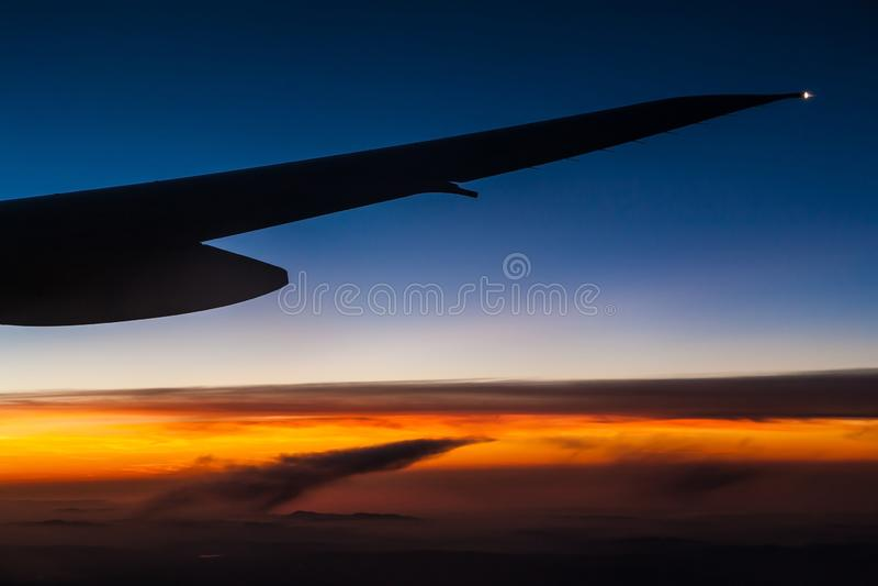 Крыло самолета над облаками на заходе солнца стоковые фото